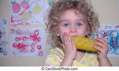 toddler cute girl eating a boiled corn. flycam shot -...