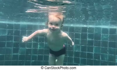 Toddler dives into the pool - Happy smiling toddler is...