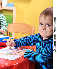 Toddler drawing in kindergarten