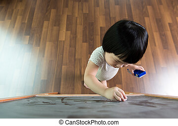 Toddler drawing on chalkboard