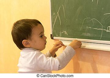 Toddler draws chalk on a blackboard
