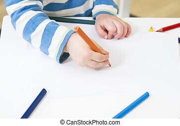 Toddler draws with an orange pencil