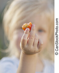 Toddler holding a hal eaten cherry tomato towards the camera. Hand and tomato in focus, toddler out of focus.