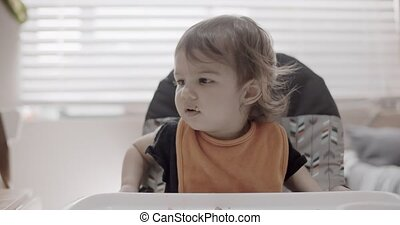 Toddler eating her dinner. Slow motion. Shot in 4K RAW on a...