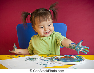 Toddler finger painting - Little happy girl discovering...