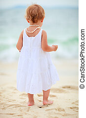 Toddler girl at seashore - Back view of toddler girl...