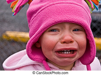 Closeup photo of a toddler girl dressed in pink crying big sad tears that will melt anyone's heart.