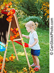 toddler girl drawing on easel