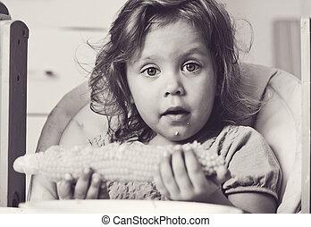 toddler girl eating corn