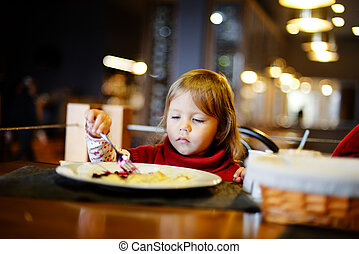 toddler girl eating in restaurant
