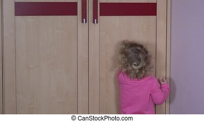Toddler girl find her mother in closet. Happy child play with mom