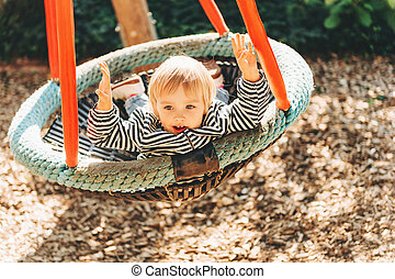 Toddler girl having fun in the park, 2-3 year old kid playing in the big swing, playground, activities for children