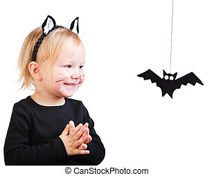 Halloween dressed toddler girl in black cat costume looking to small bat
