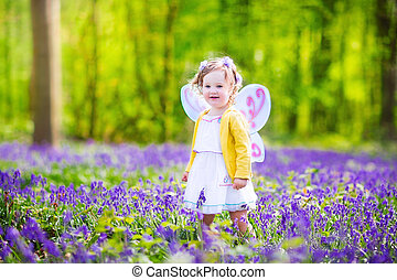 Toddler girl in fairy costume in bluebell forest - Adorable...