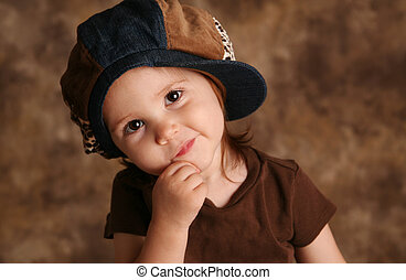 Portrait of an adorable toddler girl modeling a brown and blue jean denim hat posing for the camera