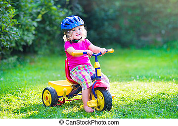 Toddler girl on a bike - Cute funny toddler girl riding her...