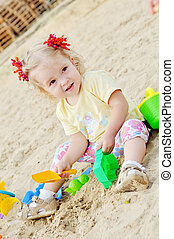 toddler girl playing in sand