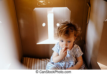 Toddler girl playing indoors in cardboard house at home.