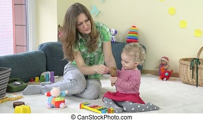Toddler girl playing instruments like metallophone and rattle with babysitter