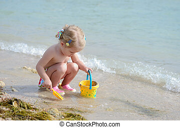 toddler girl playing on the beach