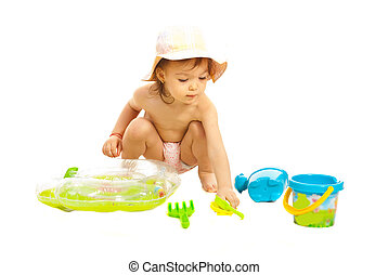Toddler girl playing with beach toys