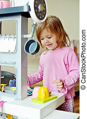 girl playing with kitchen