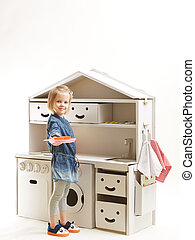 toddler girl playing with toy kitchen at home