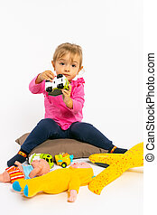 Toddler girl plays with boy toys and looks at the camera. Gender stereotypes.