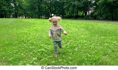 Toddler girl running through meadow in park. Happy child have fun outdoors