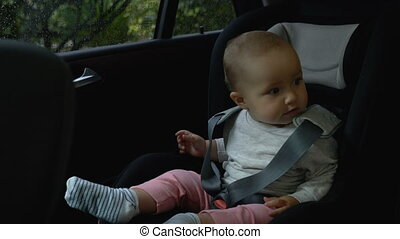 toddler girl sitting in a child seat in the car