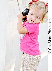 toddler girl speaking on the phone