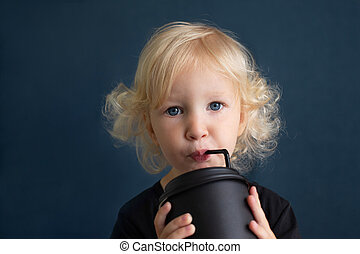 Toddler girl with blond curly hair and blue eyes drinking from big black reusable bamboo cup using straw.