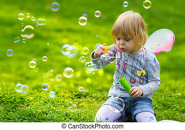 Toddler girl with butterfly wings having fun in park, blowing soap bubbles