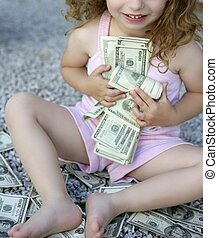 Toddler girl with lots of dollar notes