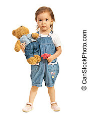 Toddler girl with teddy bear in jeans - Toddler girl holding...