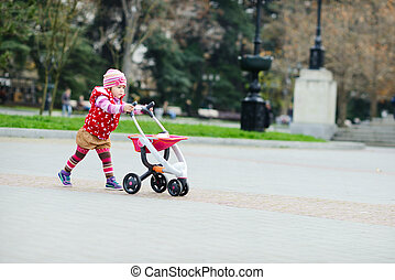 toddler girl with  toy stroller