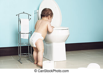 Toddler in bathroom look at the toilet - A Toddler in...