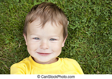 toddler in the grass - boy toddler is relaxing in the grass...