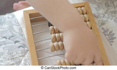 Toddler is counting with wooden abacus. Baby is playing with old wooden device. Child is learning to count.