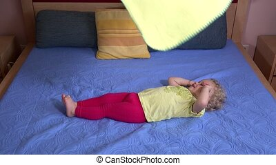 Toddler kid girl enjoy playing with yellow plaid rug laying on bed