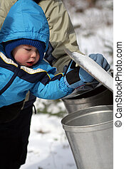 Toddler Looking in Pail - A toddler boy lifting the lid on a...