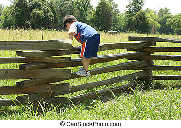 Toddler on Fence - Toddler boy climbing on old wooden fence....