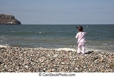 Toddler on the beach. - Happy toddler playing on a pebbly ...