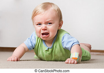 Toddler on the ground crying - A young baby having a fit on...