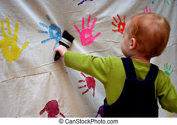 a toddler is painting on a backdrop.