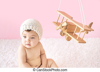 Toddler playing with a wooden plane