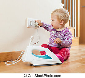 Toddler  playing with electric iron at home
