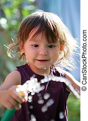 Toddler playing with garden hose