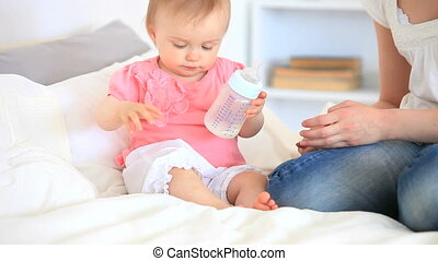 Toddler playing with her baby bottl