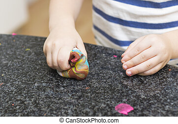 Toddler playing with playdough on kitchen bench